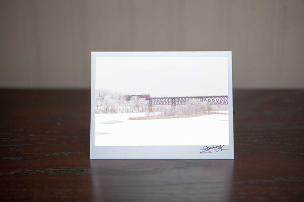 Hand made Photo greeting card perfect for Christmas that features 'WinterCrossing' a photo of a red CN train crossing an elevated train bridge above the Grand River in Cambridge Photo by Cambridge Ontario Photographer Laura Cook of Vision Photography