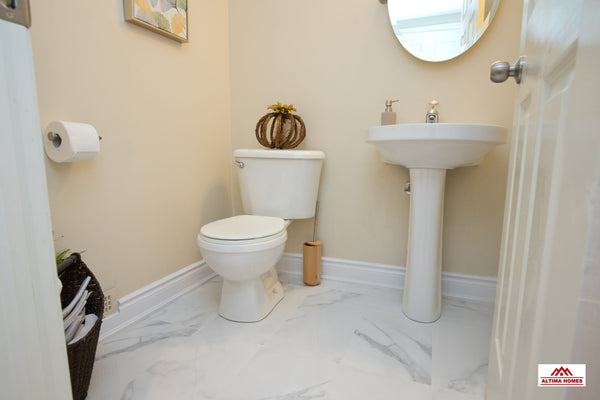 All-White Marble Floor Guest Bathroom - Altima Homes Inc.