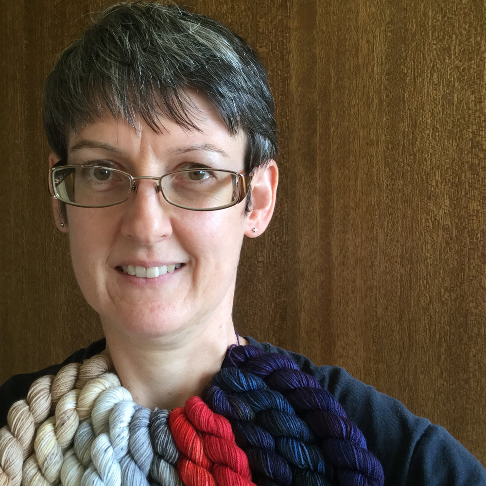 A woman with glasses wearing various coloured mini skeins of yarn around her neck