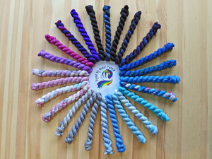 Twenty five mini skeins of yarn in various shades ranging from black and blues through greys to pinks and purples arranged in a circle on a light coloured wooden background (2017Advent Calendar Yarn Kit)