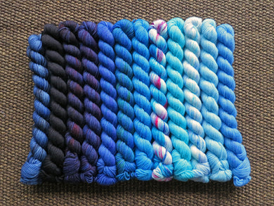 Twelve mini skeins of yarn in various shades of blue ranging from dark to light lined up on a brown woven background