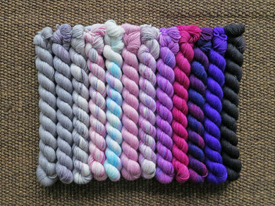 Twelve mini skeins of yarn in various colours ranging from greys through pinks to purples lined up on a brown woven background