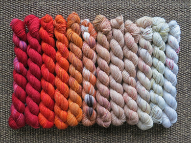 Twelve mini skeins of yarn in various colours ranging from reds through oranges to tan and beige lined up on a brown woven background