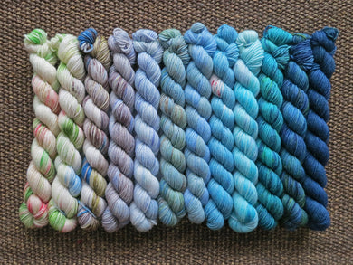 Twelve mini skeins of yarn in various colours ranging from whites and greys through blues and blue greens lined up on a brown woven background
