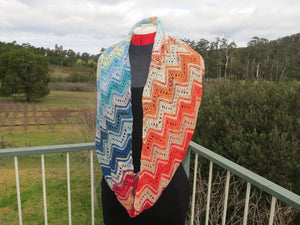 A knitted long cowl made from twenty five mini skeins arranged in stripes including dark blue greens through blues, whites, tans, oranges and reds. The cowl is looped over the neck of a dress manniquin wearing a grey and black dress standing on a balcony. In the background is a green farm and bush setting (Adventurer Cowl by Ambah O'Brien using 2018 Advent Calendar Yarn Kit)