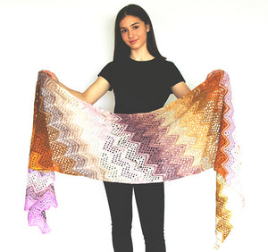 A knitted wrap made from twenty five mini skeins arranged in stripes of pinks, yellows, purples, white and tans held by a young woman wearing black standing in front of a white background (Adventurer Wrap by Ambah O'Brien)