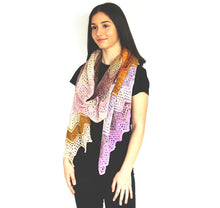 Load image into Gallery viewer, A young woman wearing black stands in front of a white background. Around her neck is looped a knitted wrap made from twenty five mini skeins arranged in stripes of pinks, yellows, purples, white and tans (Adventurer Wrap by Ambah O'Brien)