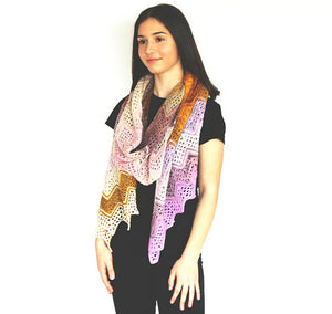 A young woman wearing black stands in front of a white background. Around her neck is looped a knitted wrap made from twenty five mini skeins arranged in stripes of pinks, yellows, purples, white and tans (Adventurer Wrap by Ambah O'Brien)