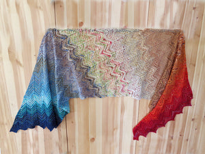 A knitted wrap made from twenty five mini skeins arranged in colour order from dark blue greens through blues, whites, and tans to oranges and reds lying on a pale wooden background (Adventurer Wrap by Ambah O'Brien using 2018 Advent Calendar Yarn Kit)