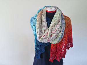 A knitted wrap made from twenty five mini skeins arranged in colour order from dark blue greens through blues, whites, and tans to oranges and reds. The wrap is looped twice around the neck of a dress manniquin wearing a dark blue dress standing in front of a cream background (Adventurer Wrap by Ambah O'Brien using 2018 Advent Calendar Yarn Kit)