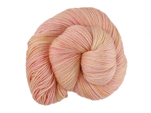 A close up of a semi-solid warm soft apricot with hints of golden yellow and red pink coloured skein of superwash bluefaced leicester, silk and cashmere 4ply fingering sock yarn presented as a spiral on a white background (Apricot Nectar on Blue Chip Stocking)