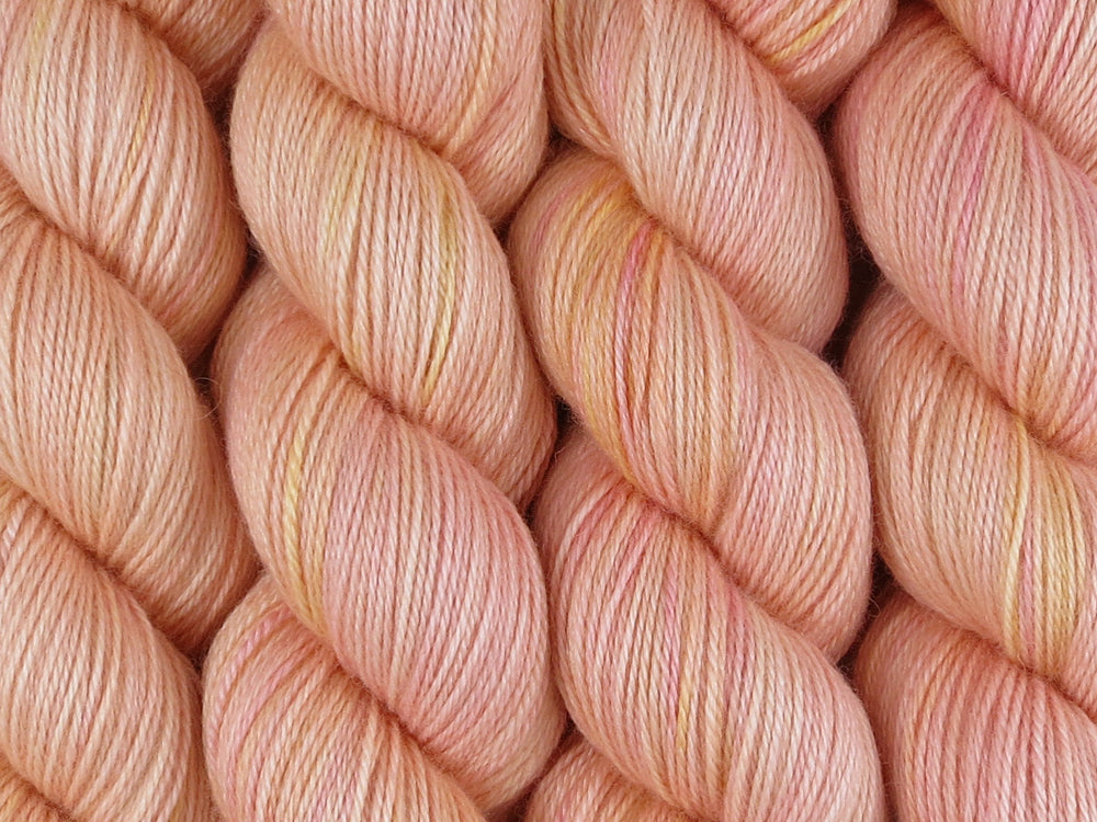 A close up of semi-solid warm soft apricot with hints of golden yellow and red pink coloured skeins of superwash bluefaced leicester, silk and cashmere 4ply fingering sock yarn (Apricot Nectar on Blue Chip Stocking)