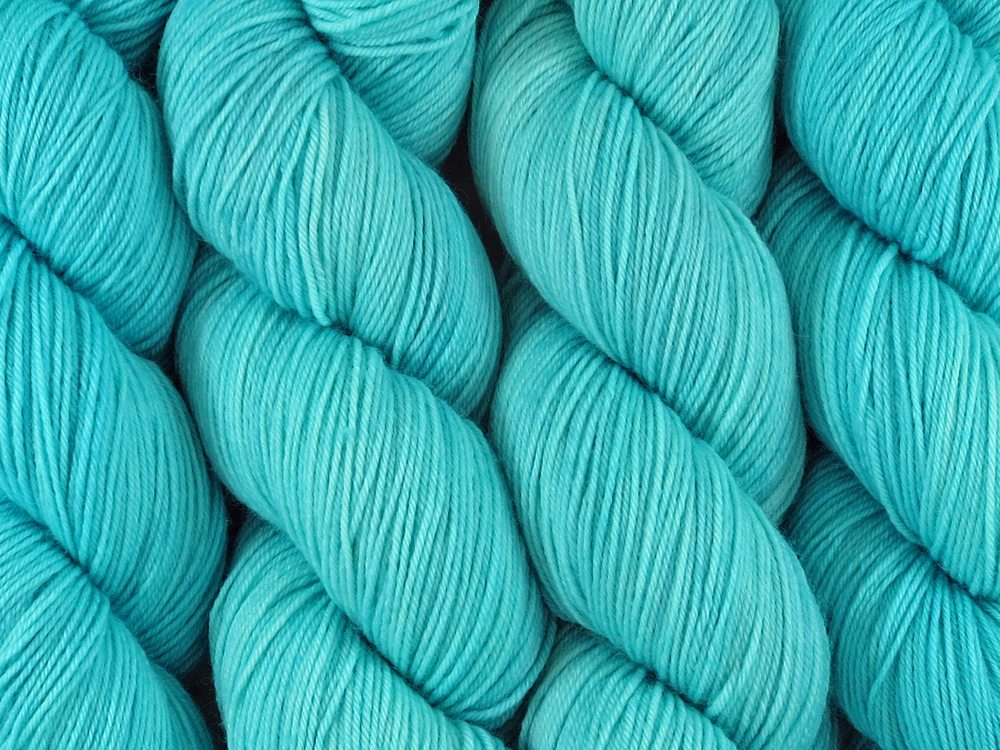 A close up of semi-solid light bright aqua blue coloured skeins of superwash merino and nylon 4ply fingering sock yarn (Aqualung on Tough Stocking)