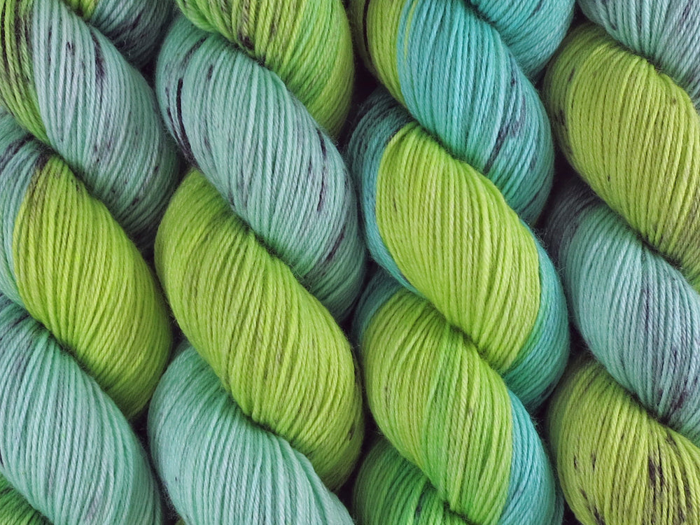 A close up of variegated bright light lime and mint greens with black speckles coloured skeins of superwash merino and nylon 4ply fingering sock yarn (Black Kangaroo Paw on Tough Stocking)