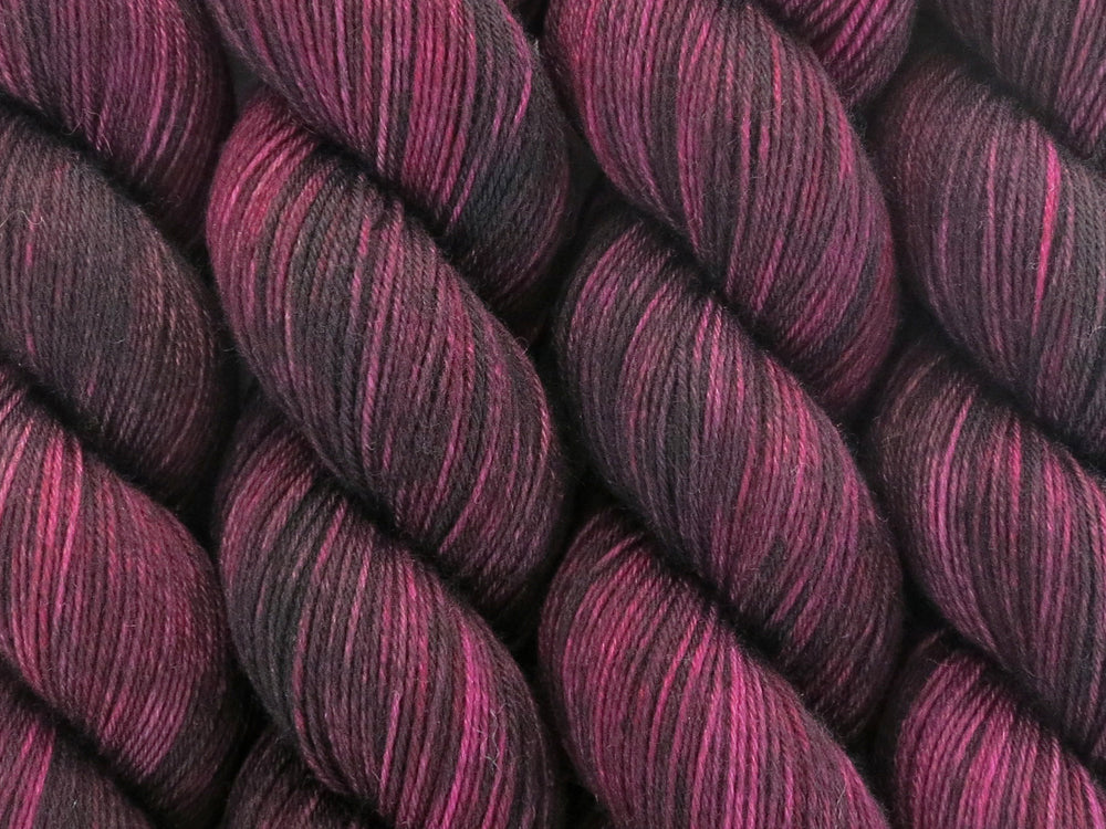 A close up of variegated black, maroon, plum and wine coloured skeins of superwash merino and nylon 4ply fingering sock yarn (Blackened Rose on Tough Stocking)