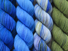 Load image into Gallery viewer, A close up of four skeins of yarn from left to right: bright mid-blues with hints of deep blue and green; tonal sky blues; variegated white, blue, green and mauve; and tonal olive greens (Blue China Orchid Caladenia MKAL Yarn Kit on Silk Stocking)