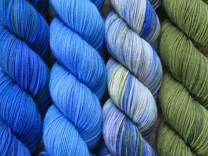 A close up of four skeins of yarn from left to right: bright mid-blues with hints of deep blue and green; tonal sky blues; variegated white, blue, green and mauve; and tonal olive greens (Blue China Orchid Caladenia MKAL Yarn Kit on Silk Stocking)