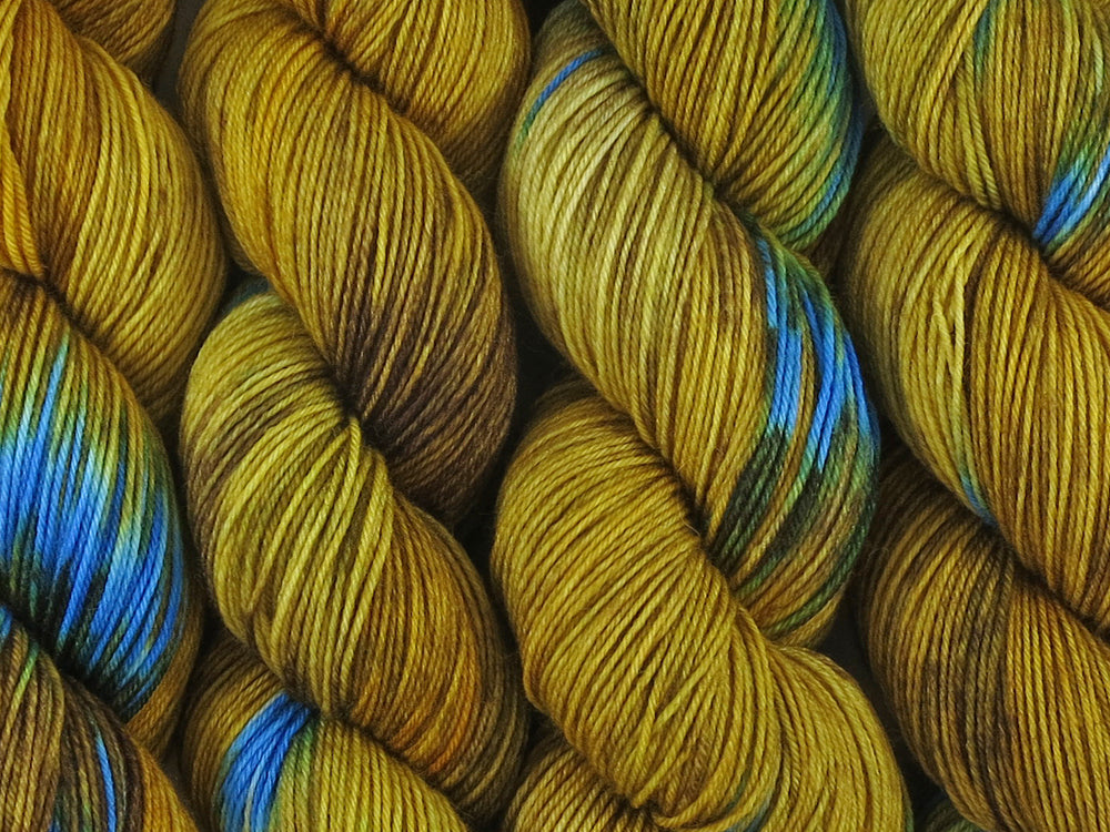 A close up of variegated yellow and brown with flashes of brilliant aqua blue coloured skeins of superwash merino and nylon 4ply fingering sock yarn (Blue Ring Octopus on Tough Stocking)