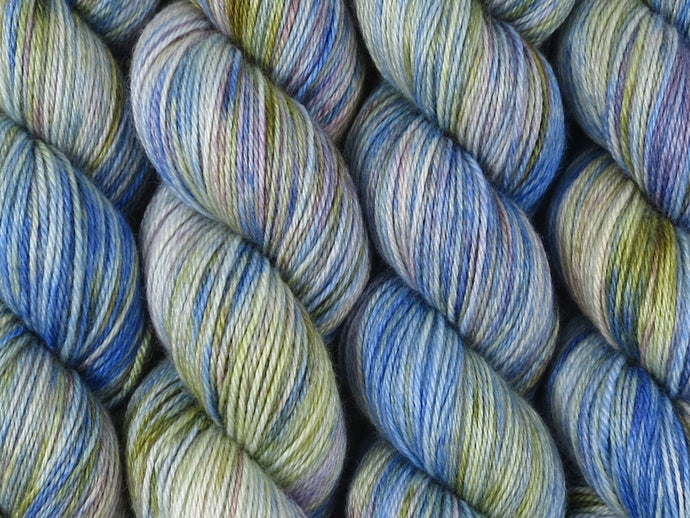 A close up of variegated cobalt blue, white, moss green and violet coloured skeins of superwash bluefaced leicester, silk and cashmere 4ply fingering sock yarn (Blue Swimmer Crab on Blue Chip Stocking)