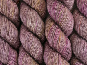 A close up of variegated brown, beige-grey, pink, purple and yellow coloured skeins of superwash merino and silk 4ply fingering sock yarn (Boronia on Silk Stocking)