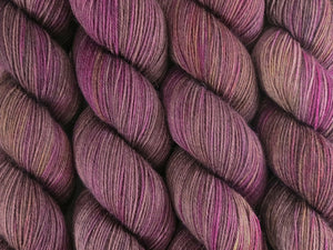 A close up of variegated brown, beige-grey, pink, purple and yellow coloured skeins of superwash merino and nylon 4ply fingering sock yarn (Boronia on Tough Stocking)