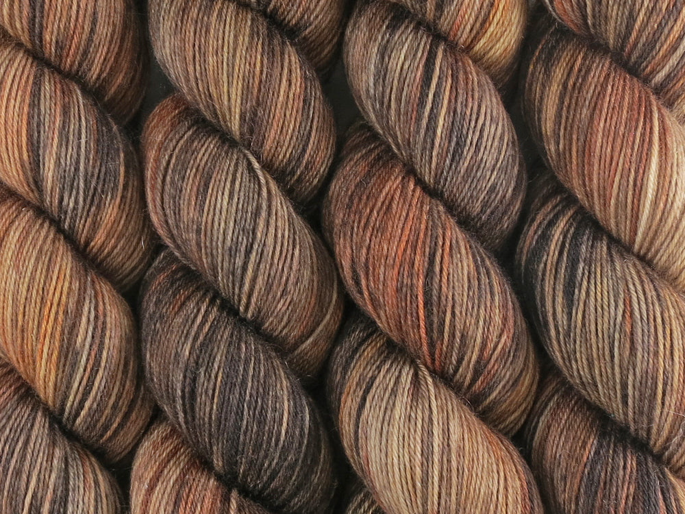 A close up of variegated ebony, chocolate, chestnut and beige brown coloured skeins of superwash merino and nylon 4ply fingering sock yarn (Bungil on Tough Stocking)