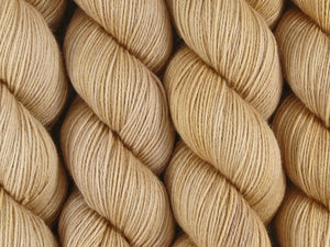 A close up of semi-solid light warm beige tan coloured skeins of superwash merino and nylon 4ply fingering sock yarn (Buttergin on Tough Stocking)