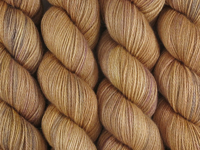 A close up of semi-solid warm tan with hints of orange, dark cocoa and maroon coloured skeins of superwash bluefaced leicester, silk and cashmere 4ply fingering sock yarn (Butterscotch on Blue Chip Stocking)