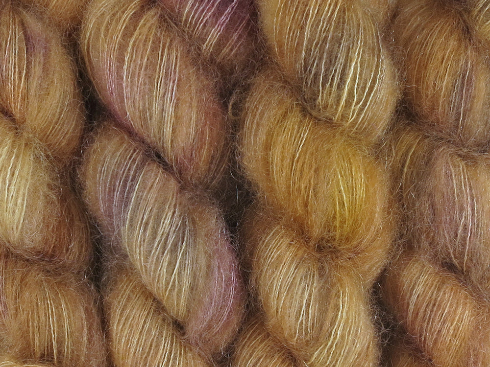 A close up of semi-solid warm tan with hints of orange, dark cocoa and maroon coloured skeins of superfine kid mohair and silk 2ply lace yarn (Butterscotch on Kid Glove Lace)