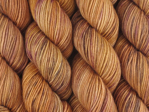 A close up of semi-solid warm tan with hints of orange, dark cocoa and maroon skeins of superwash merino, cashmere and nylon 8ply DK weight yarn (Butterscotch on Mother's Love DK)