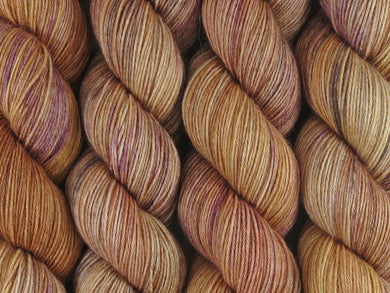 A close up of semi-solid warm tan with hints of orange, dark cocoa and maroon coloured skeins of superwash merino and nylon 4ply fingering sock yarn (Butterscotch on Tough Stocking)