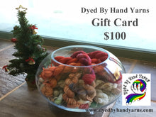 Load image into Gallery viewer, In the foreground is a round glass bowl full of multi-coloured mini skeins; behind this to the left is a decorated mini Christmas tree. This stands on a tan brown stone tile floor. There is dark grey writing in the top right hand corner that says Dyed By Hand Yarns Gift Card $100. In the bottom right hand corner is a multi-coloured logo. Under this in dark grey is a web address