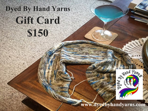 A white, brown and blue variegated piece of knitting on a short circular needle lies on a dark brown coffee table. Also on the coffee table there is a martini glass filled with light blue liquid. In the background is a cream tan flecked carpet. There is dark grey writing in the top left hand corner that says Dyed By Hand Yarns Gift Card $150. In the bottom right hand corner is a multi-coloured logo. Under this in white is a web address