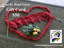 Load image into Gallery viewer, Red lace knitting on a short circular needle sits on a red skein of yarn arranged in the shape of a heart, all on top of a textured brown jute rug. There is white writing in the top left hand corner that says Dyed By Hand Yarns Gift Card $50. In the bottom right hand corner is a multi-coloured logo. Under this in white is a web address