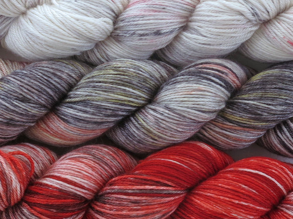 A close up of three variegated skeins of yarn from white with red and black speckles at the top to grey, black, yellow, rust red and white in the middle to reds, black and white at the bottom (Eiffel Tower Cityscape Impressionists MKAL Yarn Kit on Silk Stocking)
