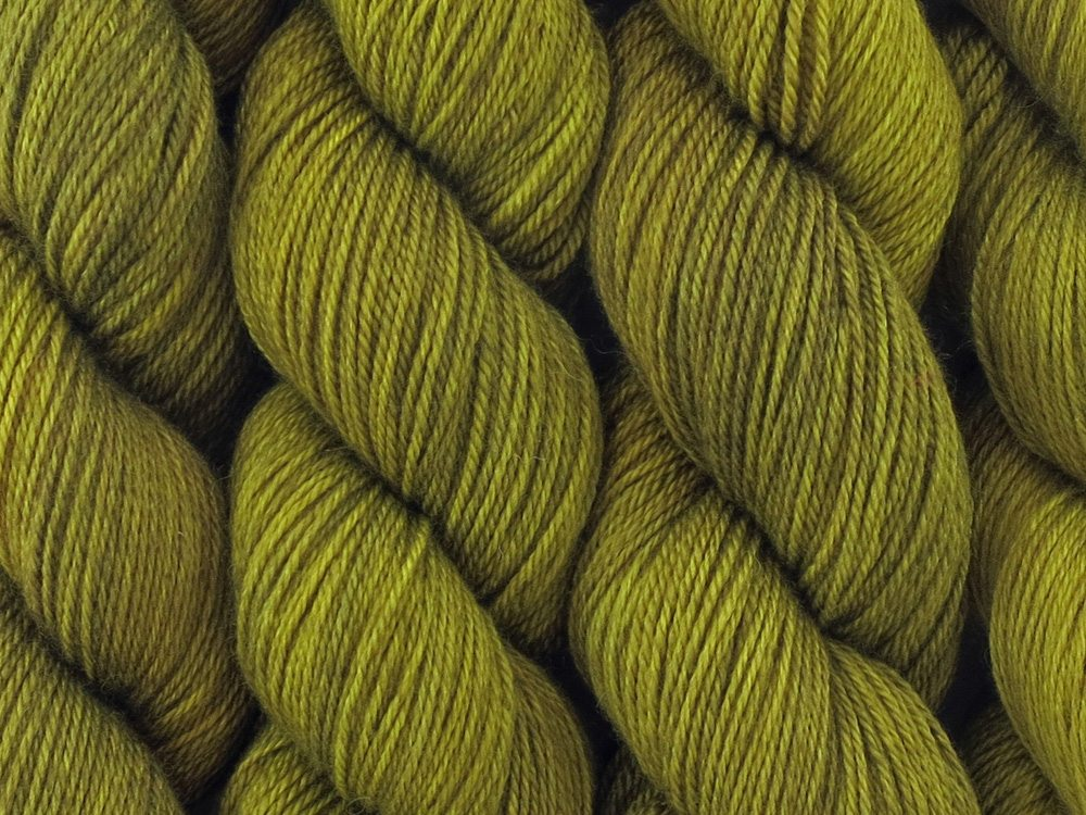 A close up of semi-solid mid-khaki green with hints of brown, chartreuse and golden tan coloured skeins of superwash bluefaced leicester, silk and cashmere 4ply fingering sock yarn (Fatigued on Blue Chip Stocking)