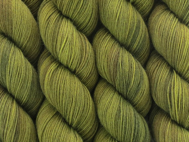A close up of semi-solid mid-khaki green with hints of brown, chartreuse and golden tan coloured skeins of superwash merino and nylon 4ply fingering sock yarn (Fatigued on Tough Stocking)