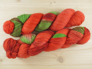 A close up of two variegated bright orange-red and Kelly green with hints of maroon skeins of non-mulesed superwash merino, cashmere and nylon 4ply fingering sock yarn (Flame Trees on Mother's Love). The skeins of yarn lies horizontally on a pale wooden background.