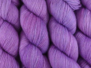 A close up of semi-solid  soft pink with hints of mauve, violet and lavender coloured skeins of superwash bluefaced leicester, silk and cashmere 4ply fingering sock yarn (Fringe Lily on Blue Chip Stocking)