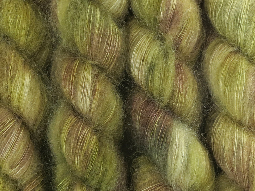 A close up of variegated khaki and forest greens, ecru and brown coloured skeins of superfine kid mohair and silk 2ply lace yarn (Gone Bush on Kid Glove Lace)