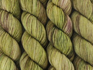 A close up of variegated khaki and forest greens, ecru and brown coloured skeins of superwash merino and nylon 4ply fingering sock yarn (Gone Bush on Tough Stocking)
