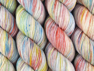 A close up of variegated white, bright yellow, orange, teal and purple coloured skeins of superwash merino and nylon 4ply fingering sock yarn (I'm Going Slightly Mad on Tough Stocking)