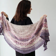 Load image into Gallery viewer, A woman with shoulder length brown hair wearing black faces away from the camera in front of a white background. Across her shoulders at arms length she holds a knitted lacey patterned shawl of pale graduated colours from white at top through pink to purple mauve at the bottom