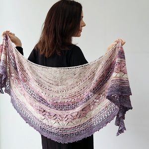 A woman with shoulder length brown hair wearing black faces away from the camera in front of a white background. Across her shoulders at arms length she holds a knitted lacey patterned shawl of pale graduated colours from white at top through pink to purple mauve at the bottom