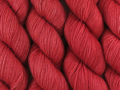 A close up of semi-solid medium red with hints of maroon and crimson coloured skeins of superwash bluefaced leicester, silk and cashmere 4ply fingering sock yarn (Japonica on Blue Chip Stocking)