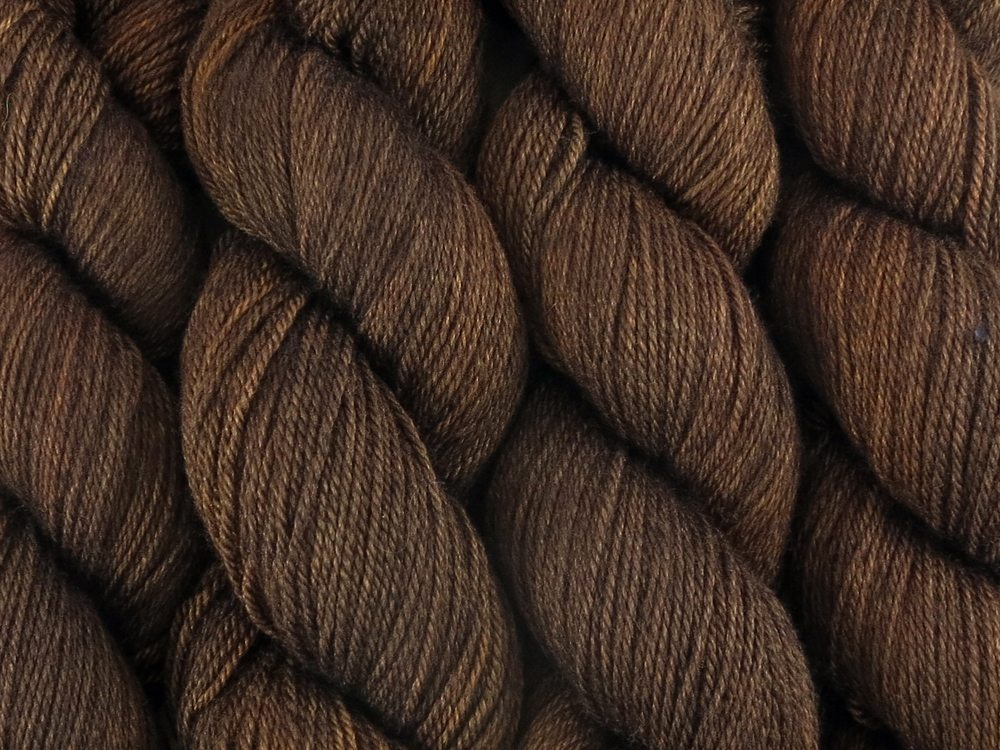 A close up of warm semi-solid deep golden brown with undertones of orange coloured skeins of superwash bluefaced leicester, silk and cashmere 4ply fingering sock yarn (Kamagong on Blue Chip Stocking)