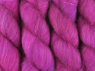 A close up of bright semi-solid cool pink with hints of mauve pink, cerise, magenta and maroon coloured skeins of superfine kid mohair and silk 2ply lace yarn (Lilly Pilly on Kid Glove Lace)