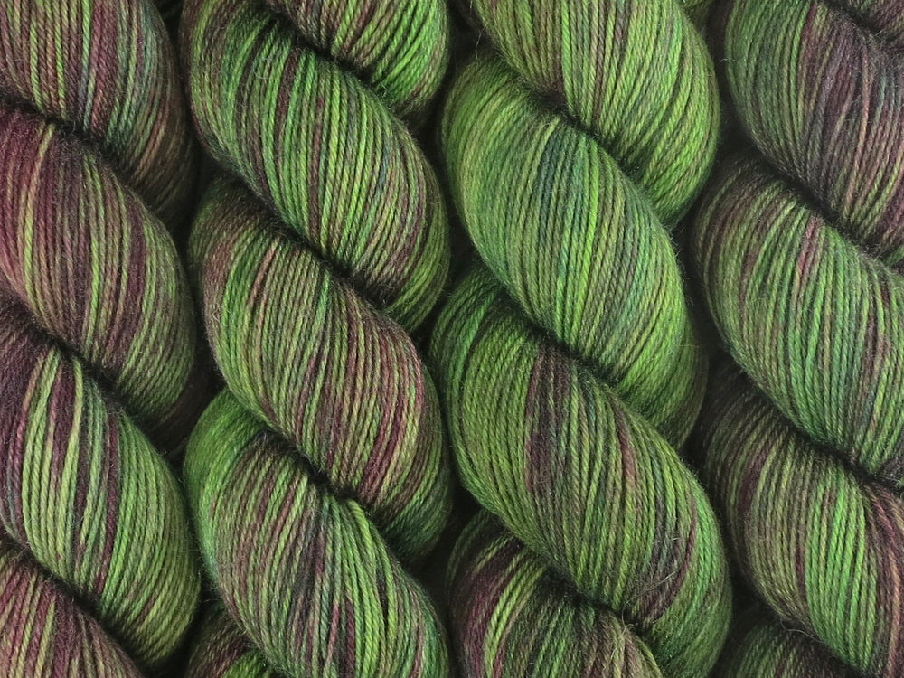 A close up of variegated bright kelly green and maroon with hints of forest and hunter greens, chartreuse and umber coloured skeins of superwash merino and nylon 4ply fingering sock yarn (Mesclun Mix on Tough Stocking)