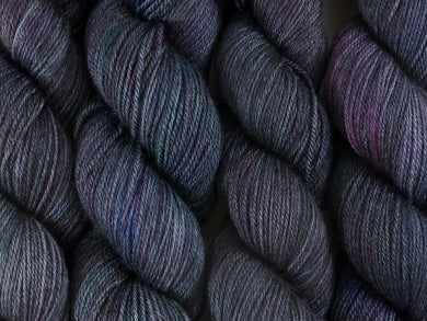 A close up of variegated black with hints of fuchsia, kelly green and royal blue coloured skeins of superwash bluefaced leicester, silk and cashmere 4ply fingering sock yarn (Nevermore on Blue Chip Stocking)