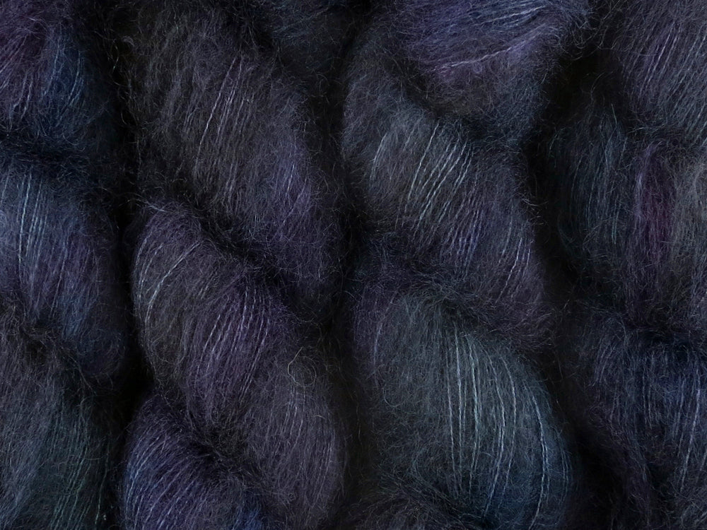 A close up of variegated black with hints of fuchsia, Kelly green and royal blue coloured skeins of superfine kid mohair and silk 2ply lace yarn (Nevermore on Kid Glove Lace)